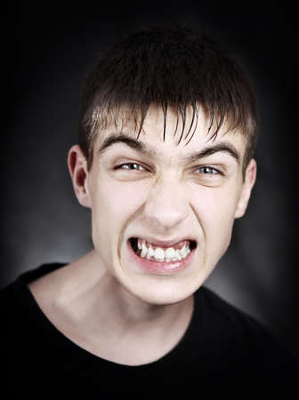 angriness: Toned Portrait of Angry Young Man on the Black Background Stock Photo