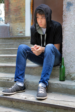 expulsion: Sad Teenager on the landing steps with a Bottle of the Beer