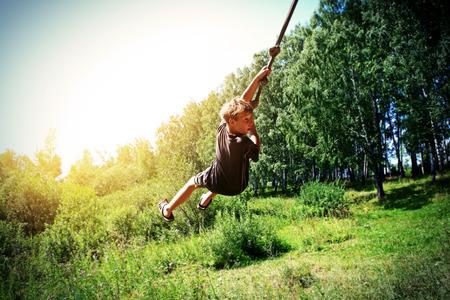 bungee jumping: Vignetting Foto de Kid Puenting en el Bosque de Verano Foto de archivo