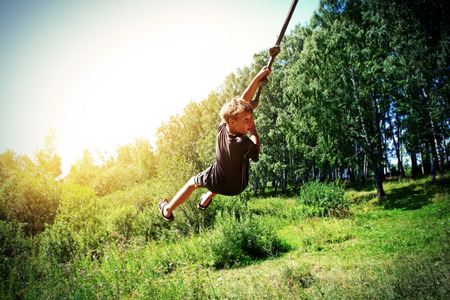 Vignetting Photo of Kid Bungee jumping in the Summer Forest