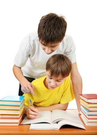 niÑos contentos: Hermano mayor y pequeño hermano hacer la tarea en el fondo blanco