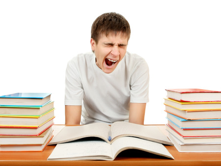 jaded: Tired Student Yawning on the School Desk Isolated on the White