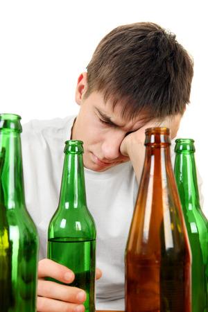 jovenes tomando alcohol: Triste y deprimido hombre joven en la adicci�n del alcohol en el fondo blanco Foto de archivo