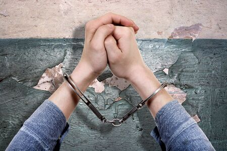 part prison: Handcuffs on Hands on the Old Wall Background closeup Stock Photo