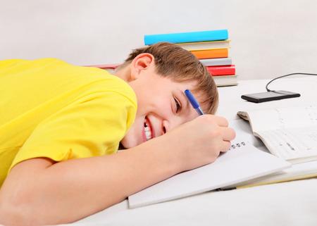boyhood: Cheerful Kid doing Homework on the Sofa at the Home Stock Photo