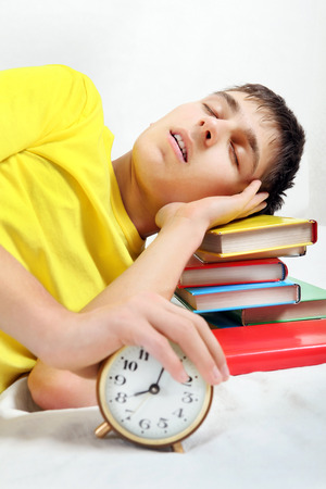 reveille: Teenager sleep on the Books with Alarm Clock Stock Photo