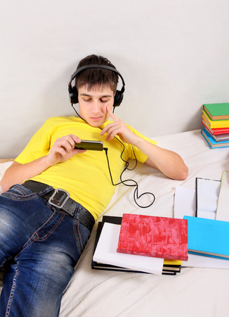 wearied: Bored Student in Earphones with the Books on the Bed