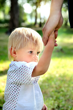 intractable: Sad Child hold the Parent Hand in the Summer Park Stock Photo