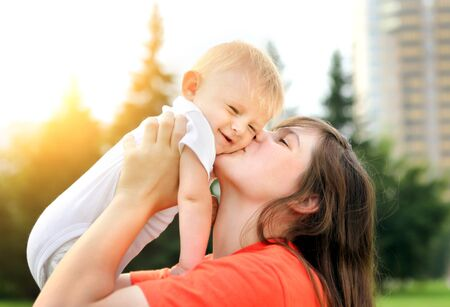 mama: Happy Mother kiss a Little Baby outdoor