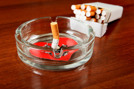 insult: Cigarette in Ashtray with Heart Shape on the Table