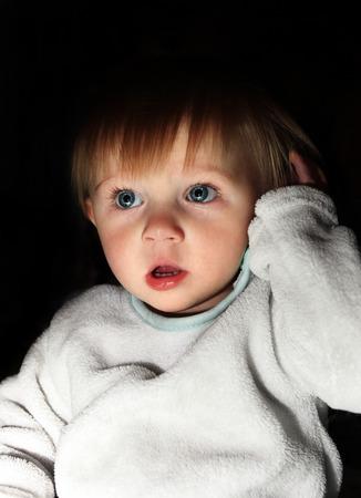 scared child: Asustado del ni�o del muchacho del retrato en el cuarto oscuro