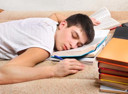 kavkazský: Unavený Teenager spát na pohovce s knihami Reklamní fotografie