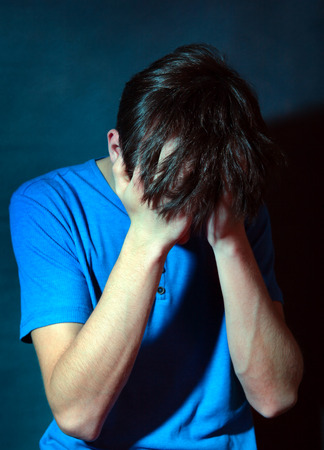 sorrowful: Toned Photo of the Sorrowful Teenager in the Dark Room Stock Photo