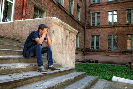 expulsion: Sad Young Man on the landing Steps of the Old House
