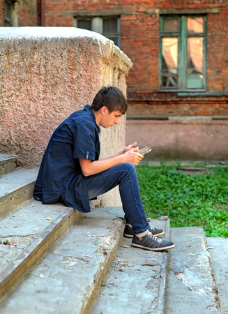 loner: Teenager with Tablet Computer on the landing Steps of the Old House