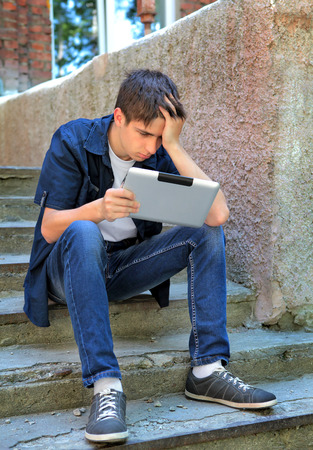 portable failure: Sad Teenager with Tablet Computer on the landing steps of the House