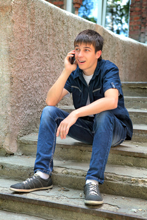 gladden: Cheerful Teenager with Cellphone on the landing steps