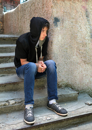 outcast: Sad Teenager in the Hood on the landing steps of the Old House