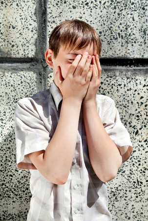 troubled: Sad and Troubled Kid by the Wall hide the Face Stock Photo
