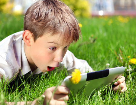 surprised kid: Surprised Kid with Tablet Computer on the Summer Meadow Stock Photo