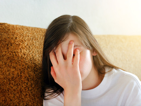 girl sitting down: Sad and Troubled Teenage Girl at the Home