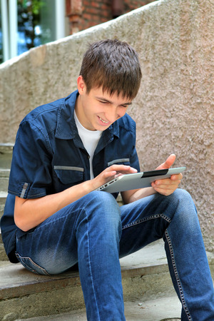 gladden: Cheerful Teenager with Tablet Computer on the Street