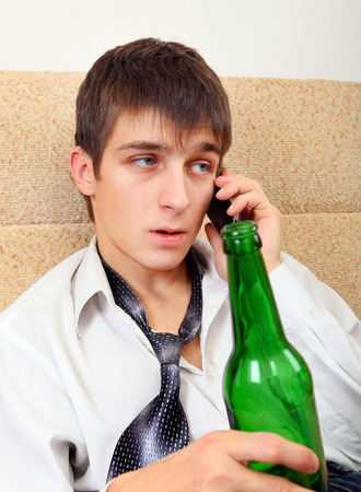necktie beer: Young Man with Bottle of the Beer and Cellphone on the Sofa at the Home Stock Photo