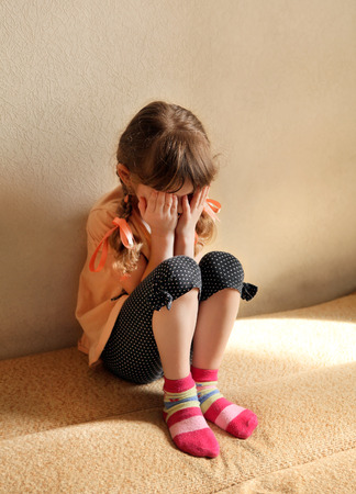 oppress: Sad Little Girl on the Bed in the Domestic Room Stock Photo