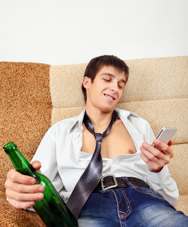 beer and necktie: Drunken Young Man with Bottle of the Beer and Cellphone on the Sofa at the Home