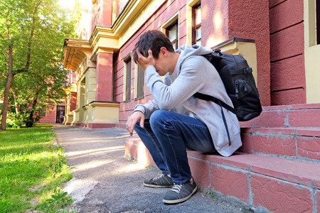 Sad Young Man with Knapsack on the Porch of the House Stock Photo