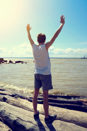 gladden: Toned Photo of Happy Young Man with Hands Up at the Seaside Stock Photo