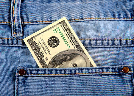 pickpocket: Hundred Dollars in the Pocket of the Jeans closeup Stock Photo
