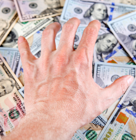 covet: Human Hand on the American Dollars Background