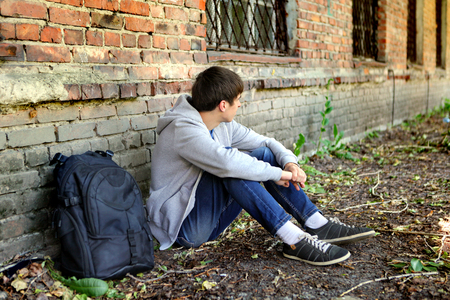 Droevige tiener in de buurt van de bakstenen muur van het oude huis
