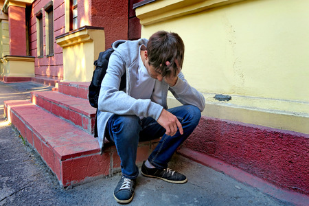 knapsack: Sad Young Man with Knapsack on the Porch of the House Stock Photo