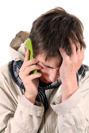 distress: Sad Young Man with Cellphone Isolated on the White Background