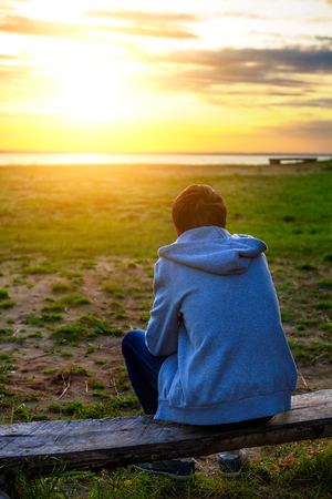 remorse: Teenager on the Nature at Sunset with the Sun in the Background