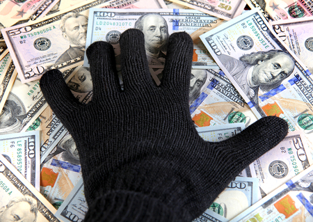 thievery: Hand in Black Glove on the American Dollars Background Stock Photo