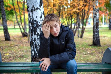 Zdůraznil Kid sedí na lavičce v parku na podzim Reklamní fotografie