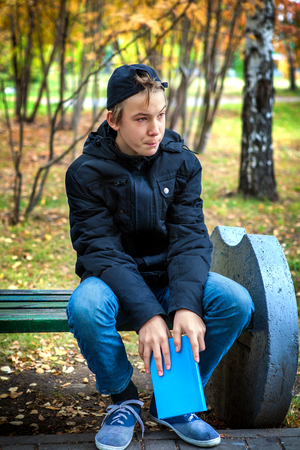 boy sitting: Sad Teenager with the Book in the Autumn Park