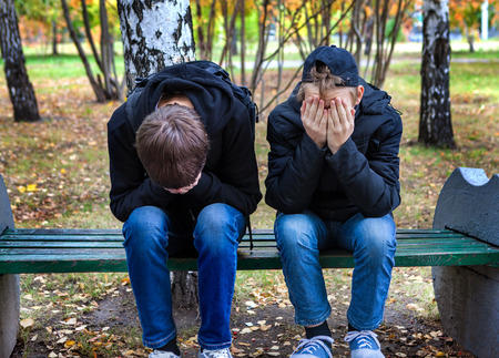 brothers: Two Sad Boys on the Bench in the Autumn Park