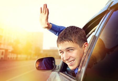 joyride: Cheerful Young Man sit in the Car on the City Street Stock Photo