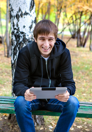 gladden: Cheerful Young Man with Tablet Computer in the Autumn Park