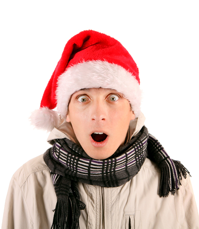 young man: Surprised Young Man in Santas Hat Isolated On The White Background Stock Photo