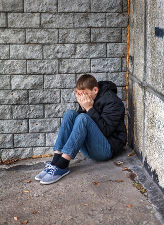 distress: Sad Teenager sit in the Corner on the Street