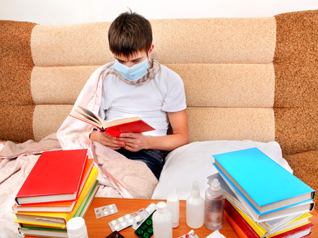 grippe: Sick Young Man in Flu Mask read the Books on the Sofa at the Home Stock Photo