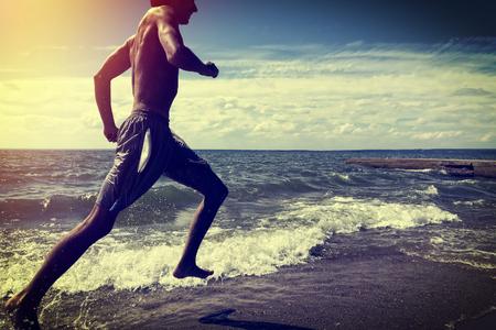 corriendo: Foto virada del Hombre corriendo en la playa Foto de archivo