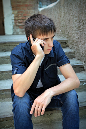 ire: Sad Teenager with Cellphone on the City Street Stock Photo
