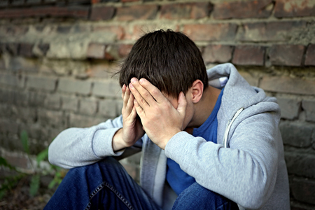 downcast: Sad Young Man sit on the Brick Wall Background Stock Photo