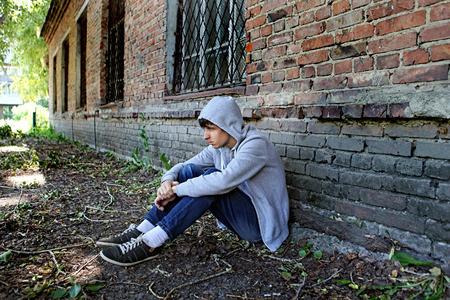 Sad Teenager sit on the Brick Building Background